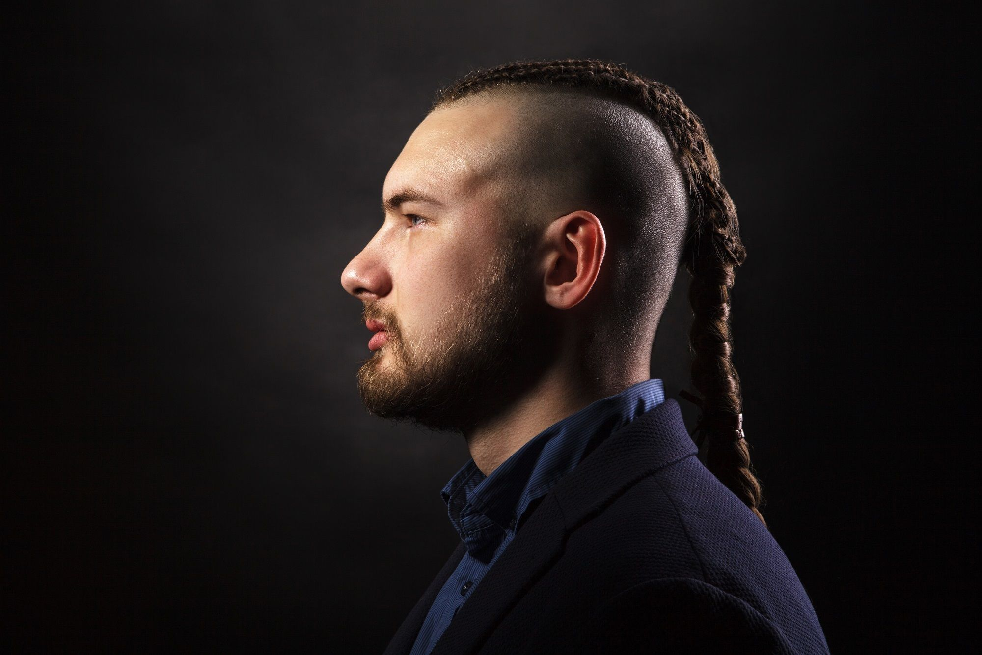 Man ponytail: Profile shot of a man with undercut dreadlock ponytail against a dark background