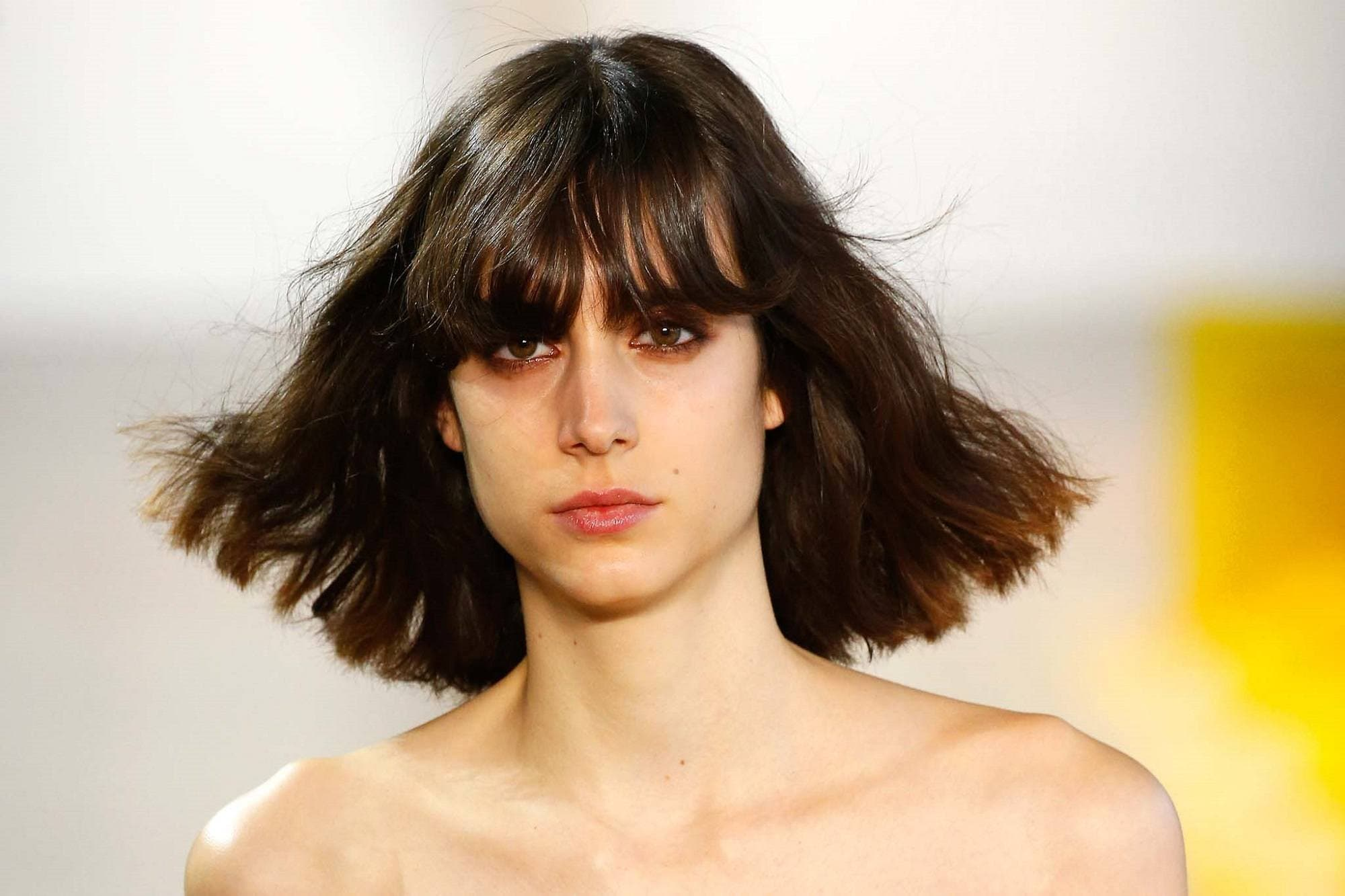 New York Fashion Week hair: Closeup shot of a woman with shoulder length dark hair with bangs
