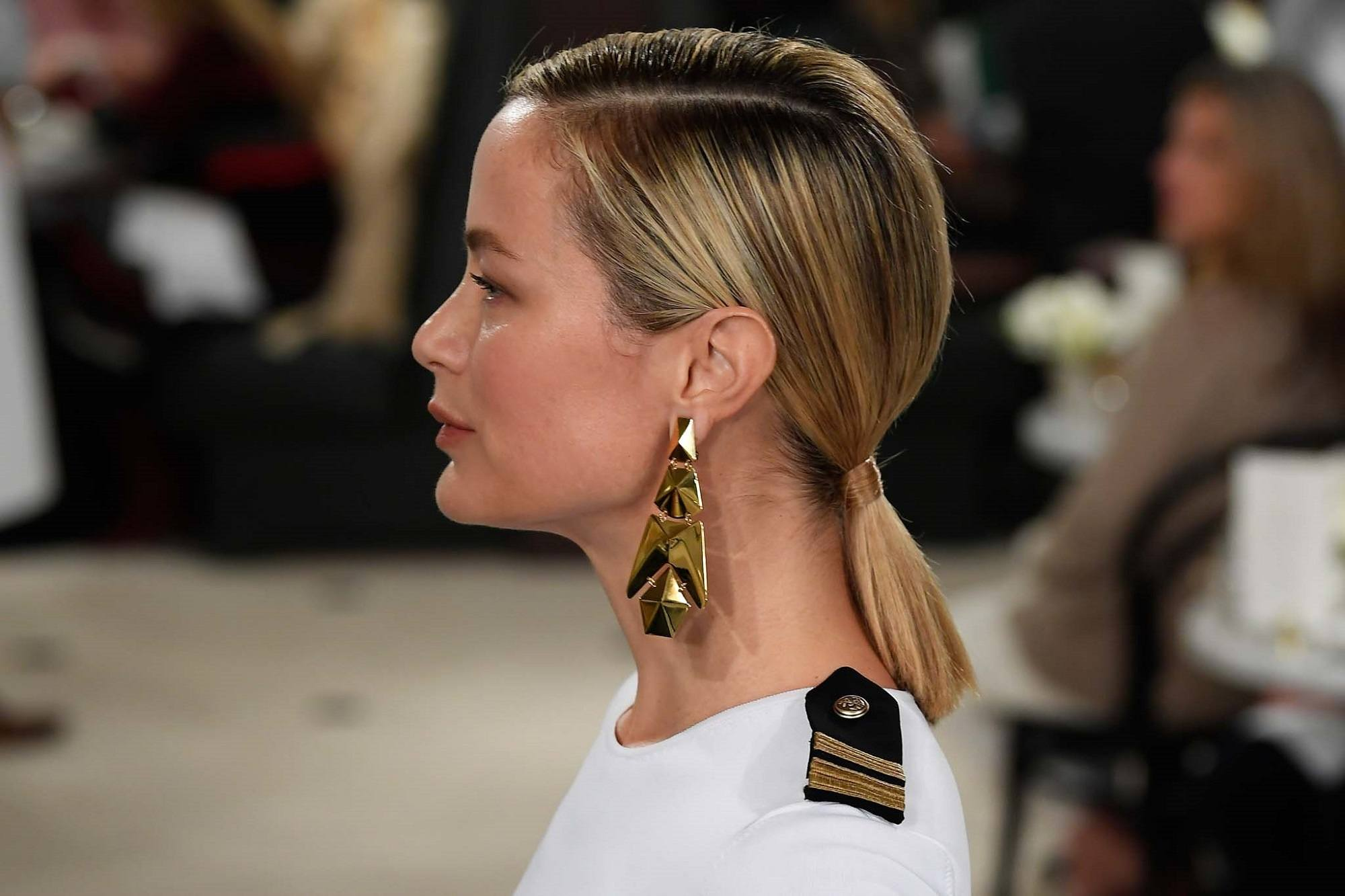 New York Fashion Week Hair: Side view shot of a woman with straight blonde hair in a ponytail wearing big earrings and white top