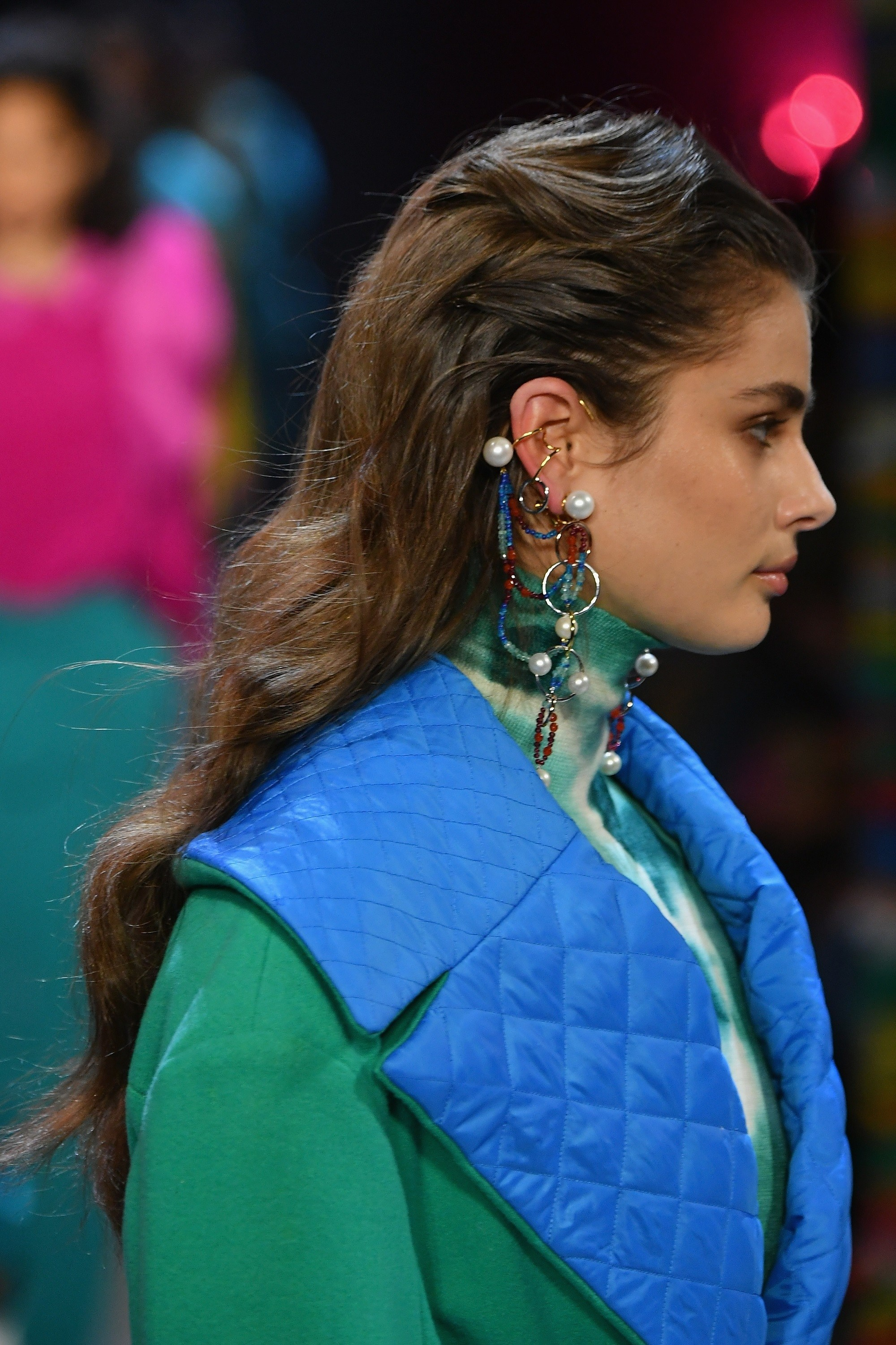 NYFW Hair must-haves: Side view of a model with long dark brown wavy hair wearing a blue vest and green top