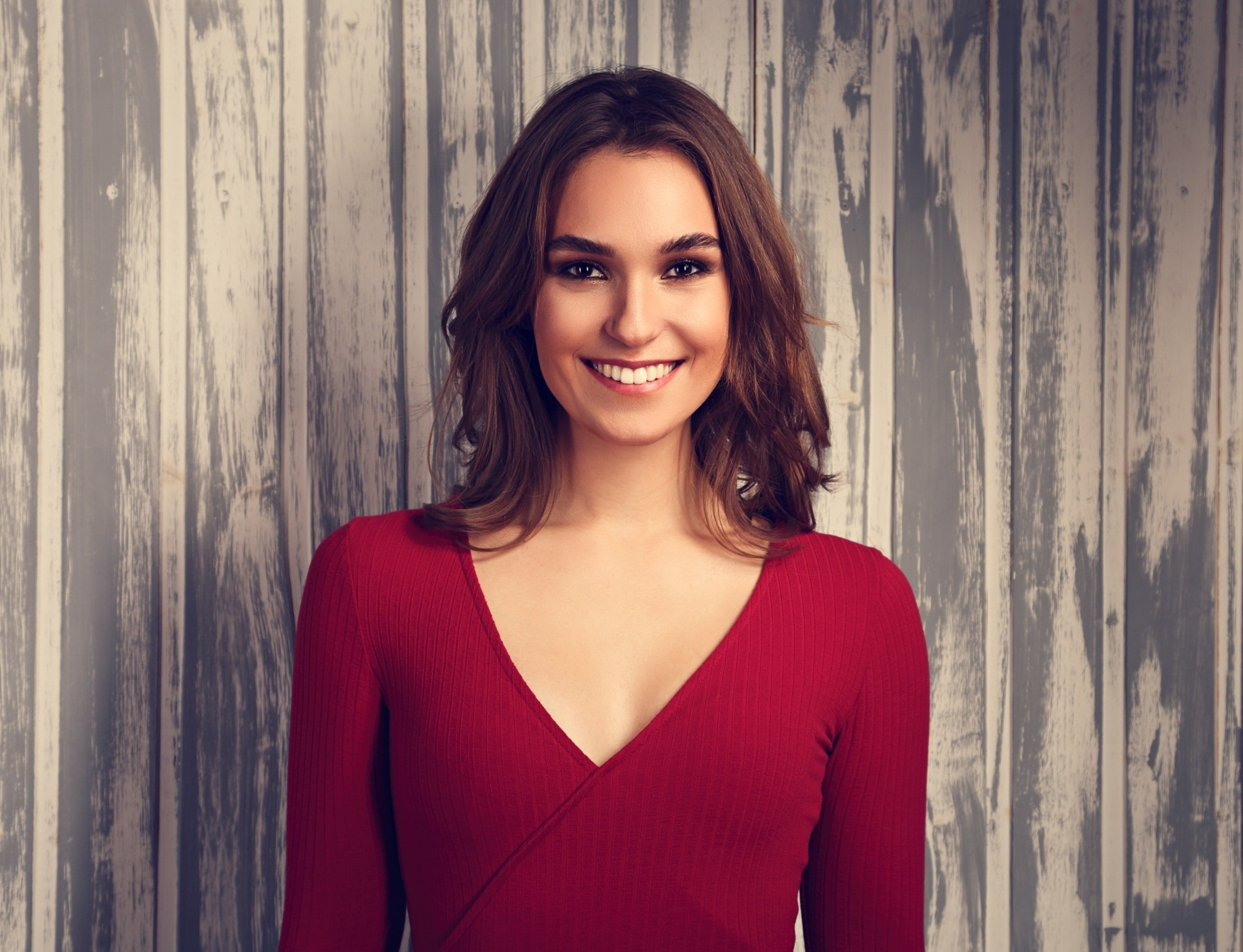Party hairstyles for medium hair: Woman with medium-length brown hair wearing a red top against a wooden background