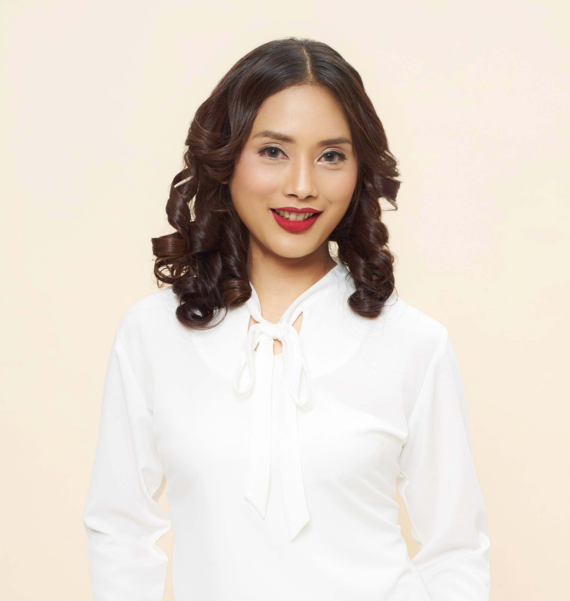 Party hairstyles for medium-length hair: Closeup shot of an Asian woman with shoulder-length wavy hair wearing a white blouse