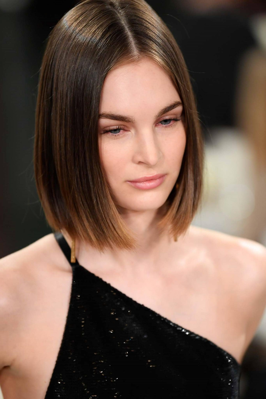 Party hairstyles for medium hair: Closeup shot of a woman with straight dark medium-length hair