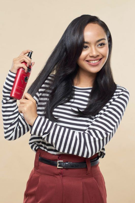 Pin up hair: Asian woman spraying heat protectant on her long black hair
