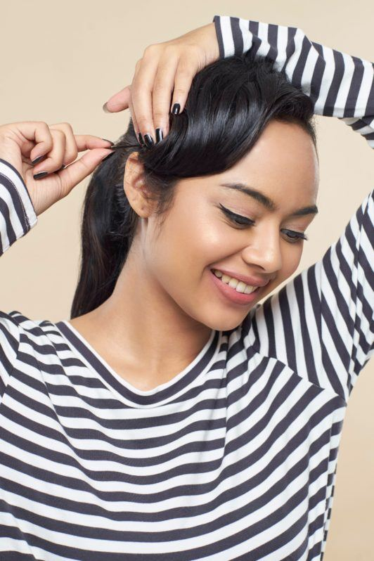 Pin up hair: Closeup shot of an Asian woman with long black hair pinning her bangs