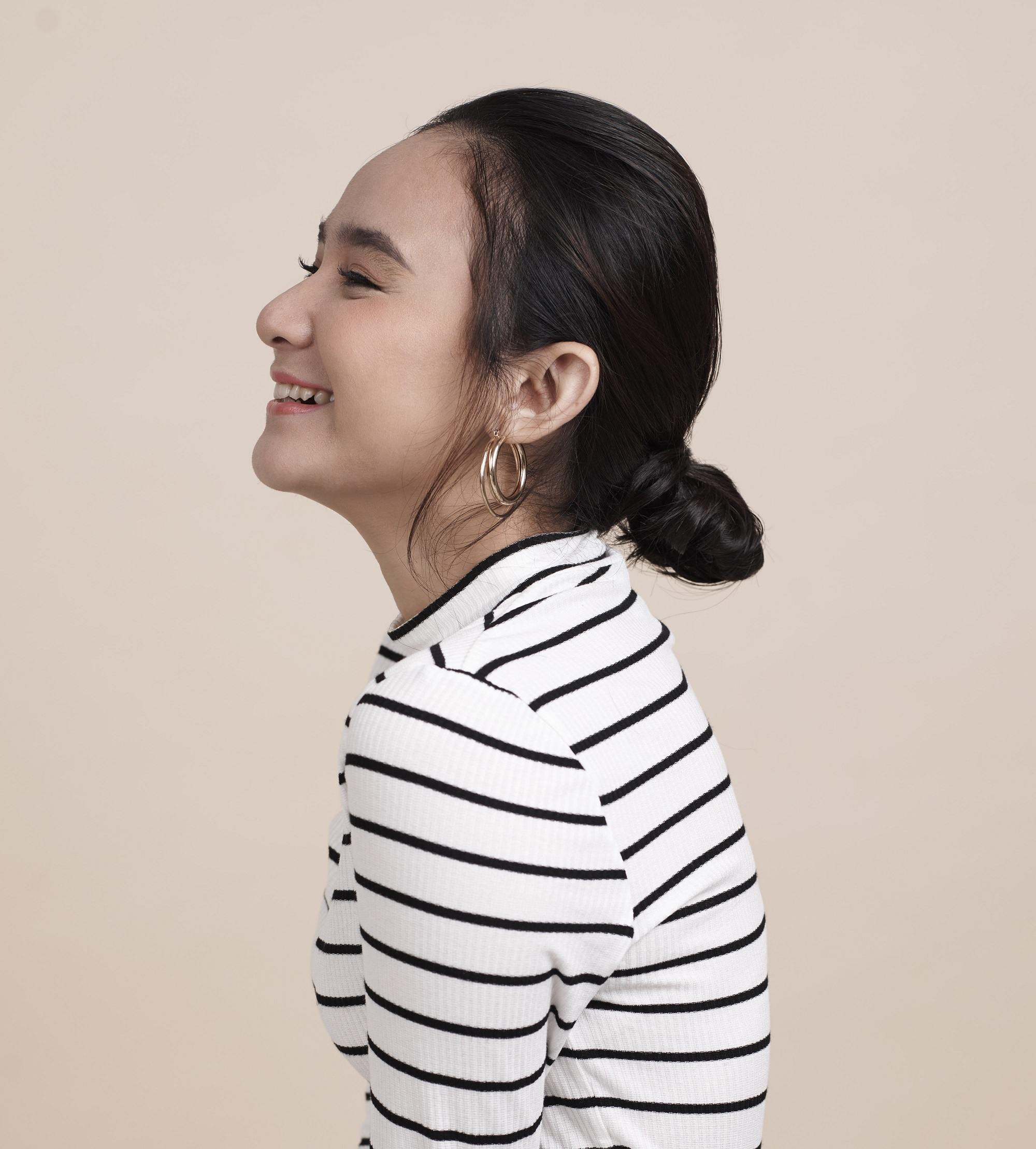 Romantic hairstyles for short hair: Side view shot of an Asian woman with short black hair in a low bun