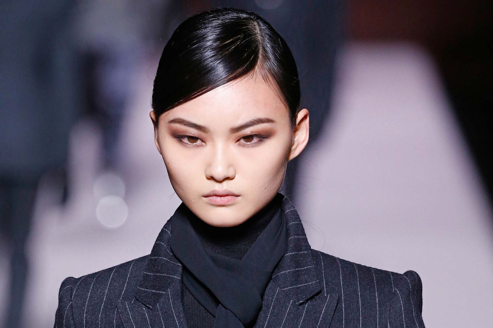 Side sweep hair: Closeup of an Asian woman with black hair with a deep side part wearing dark winter clothes