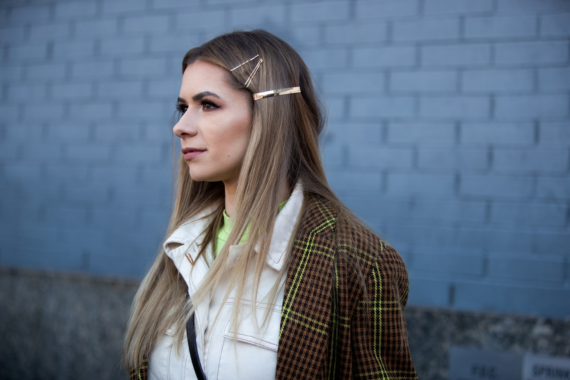 Street style hair inspiration: Woman with long straight blonde hair wearing hair clips and a brown jacket outdoors