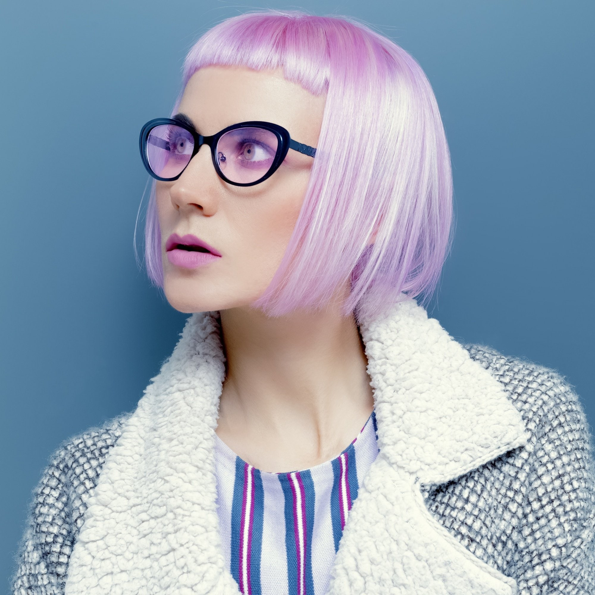 Baby bangs for short hair: Closeup shot of a woman with short pink hair with baby bangs wearing eyeglasses