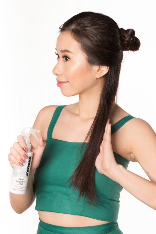 Half updo with bun: Asian woman with styled long dark hair spraying heat protectant
