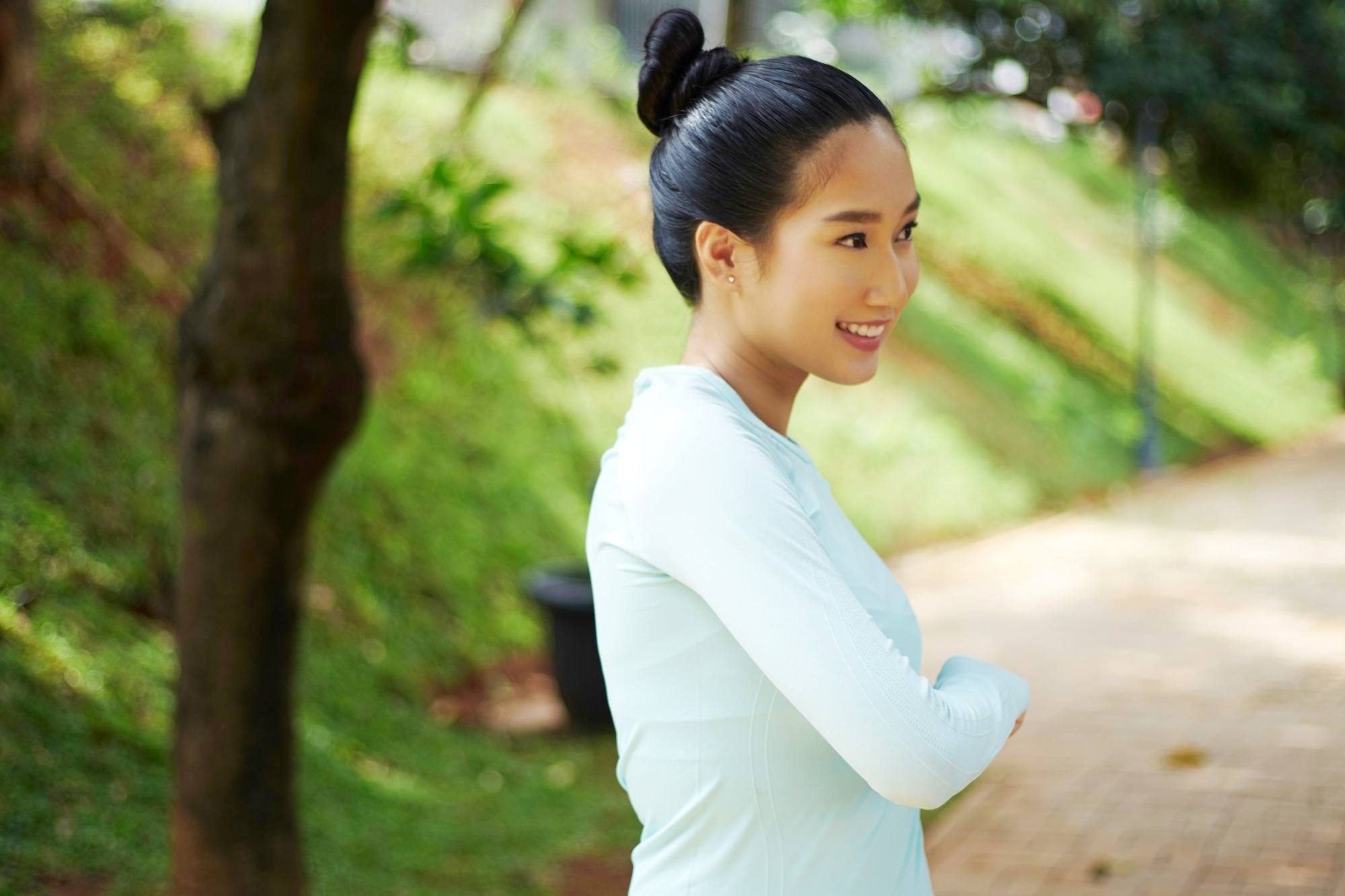 International Women's Day: Asian woman with black hair in a ballerina bun wearing a long-sleeved top outdoors