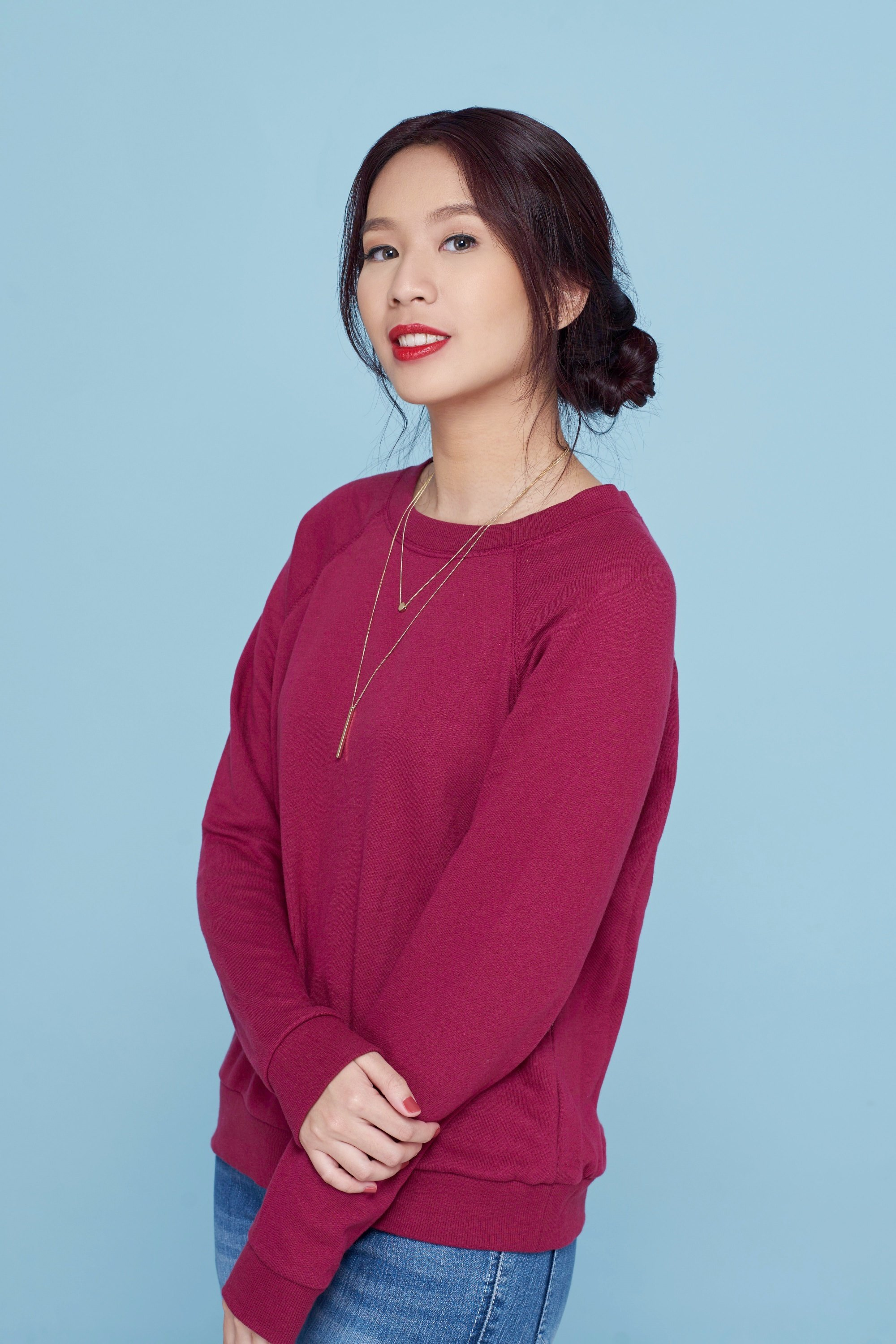 International Women's Day: Asian woman with long black hair in a banana bun wearing a dark pink sweater