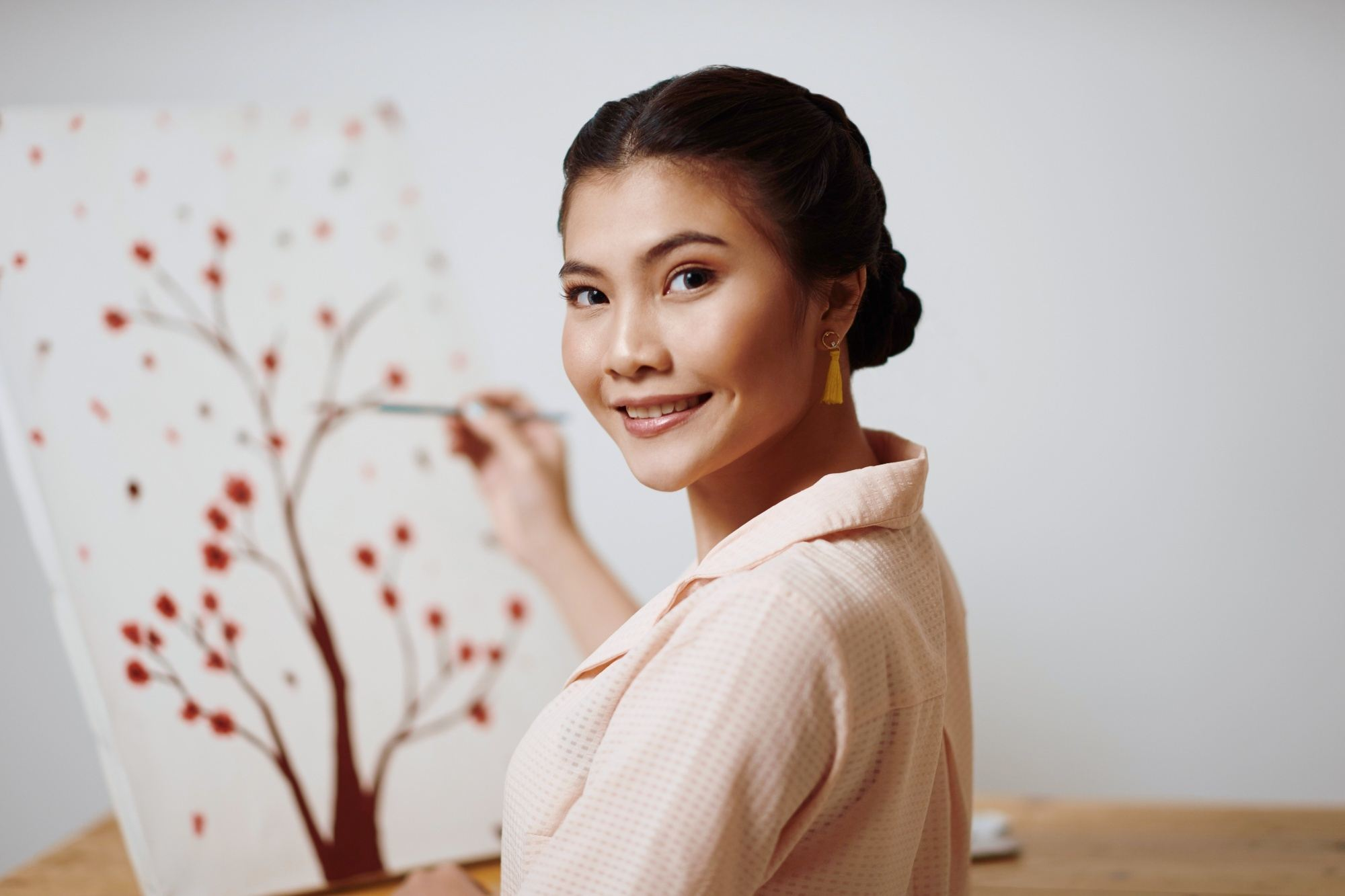 International Women's Day: Closeup shot of an Asian woman with black hair in double Dutch braid bun painting a tree on a canvas