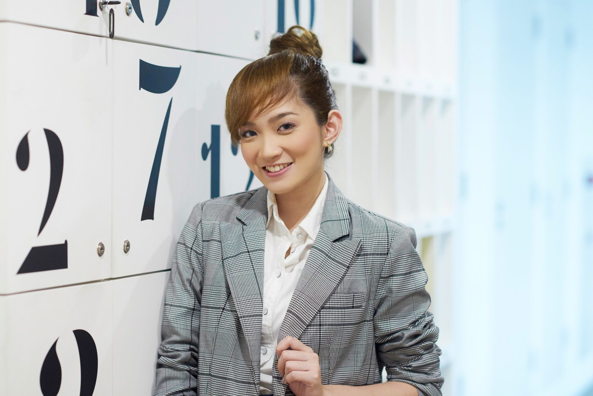 International Women's Day: Asian woman with long brown hair in a bun with faux bangs wearing a gray blazer