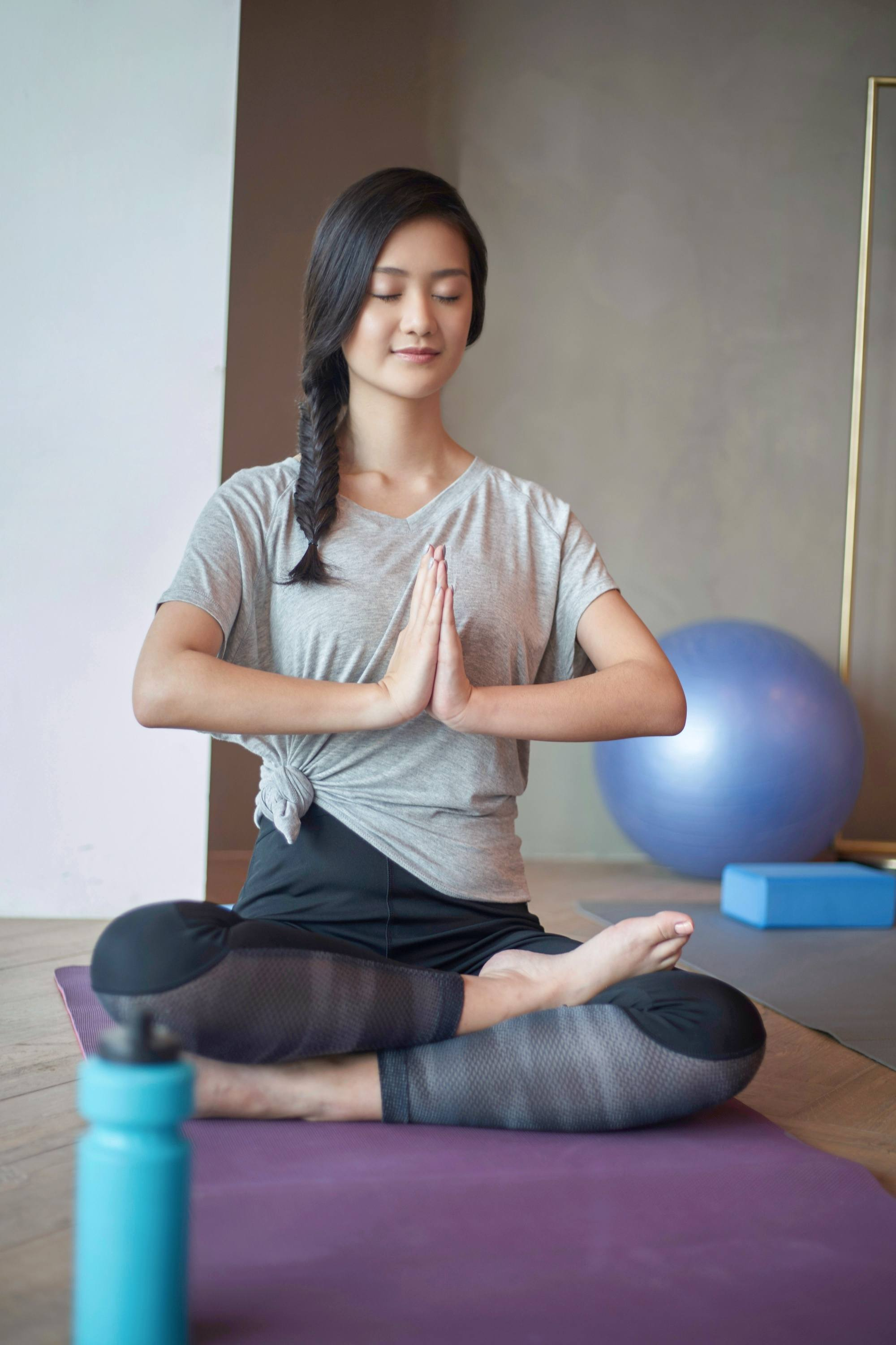 International Women's Day: Asian woman with long black hair in fishtail braid doing yoga in a room