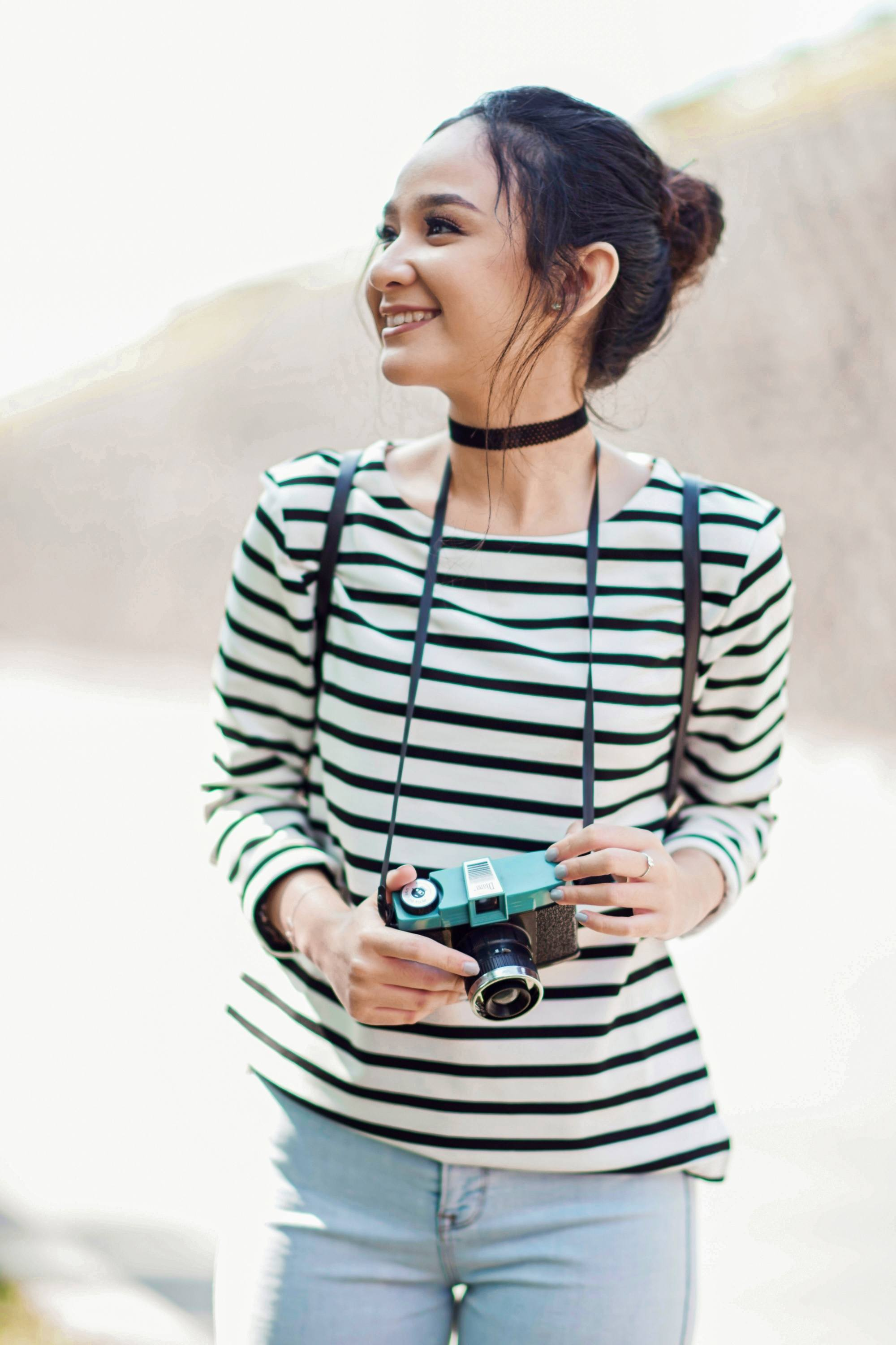 International Women's Day: Asian woman with long black hair in a messy bun wearing a striped shirt and holding a camera