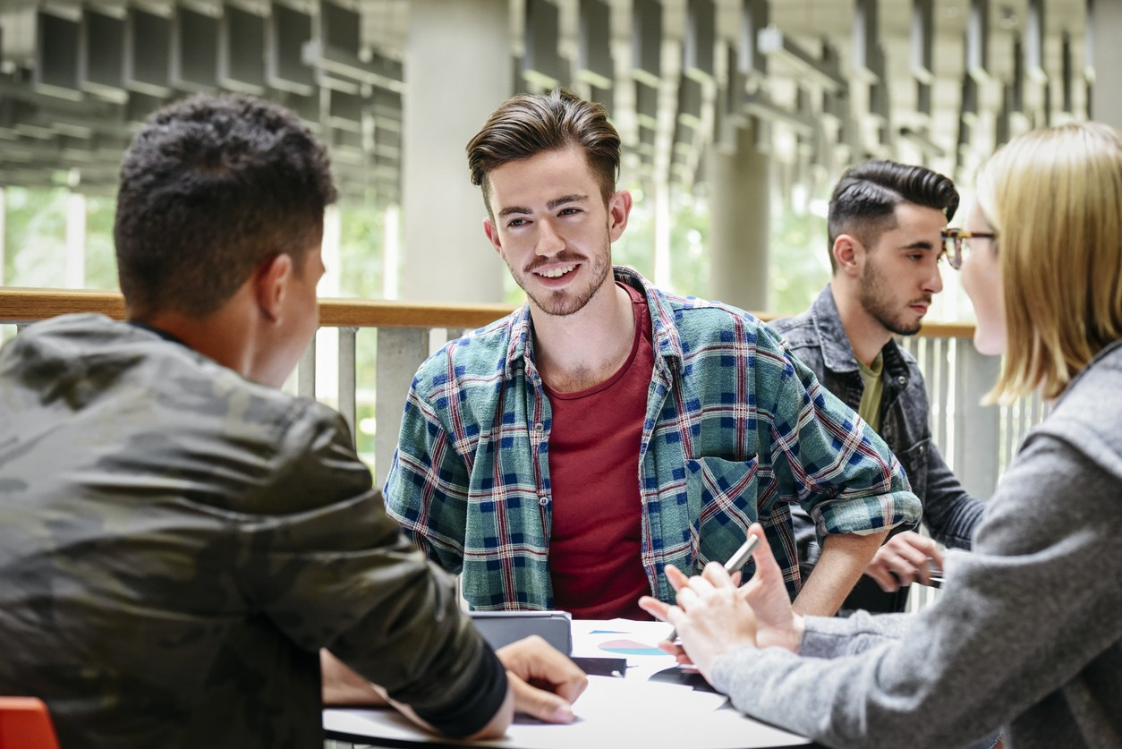 Group of students talking around table, man in his 20s with moustache and goatee smiling with cheerful expression