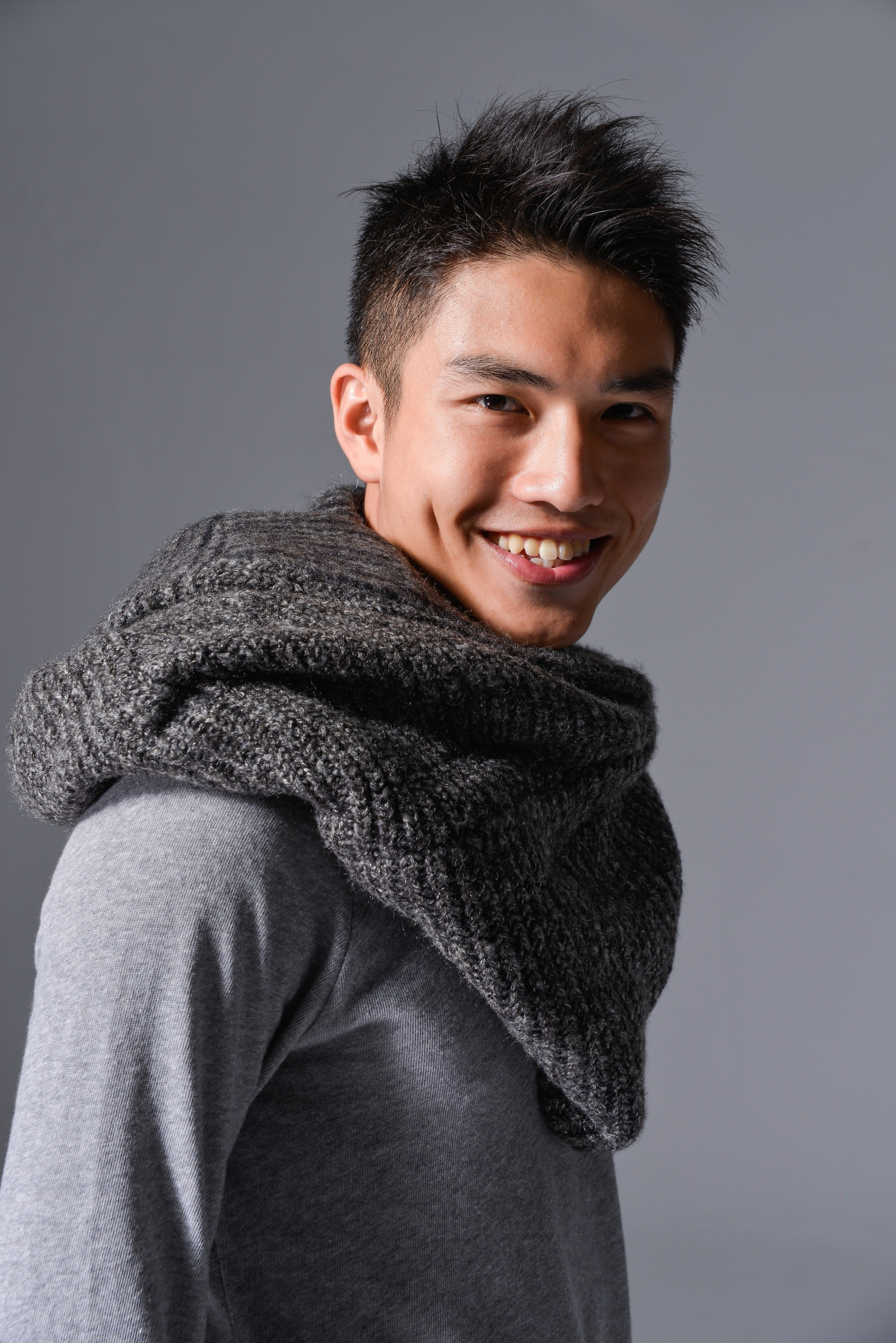 Messy hairstyles men: Man with short black messy layered hair wearing a gray scarf and shirt