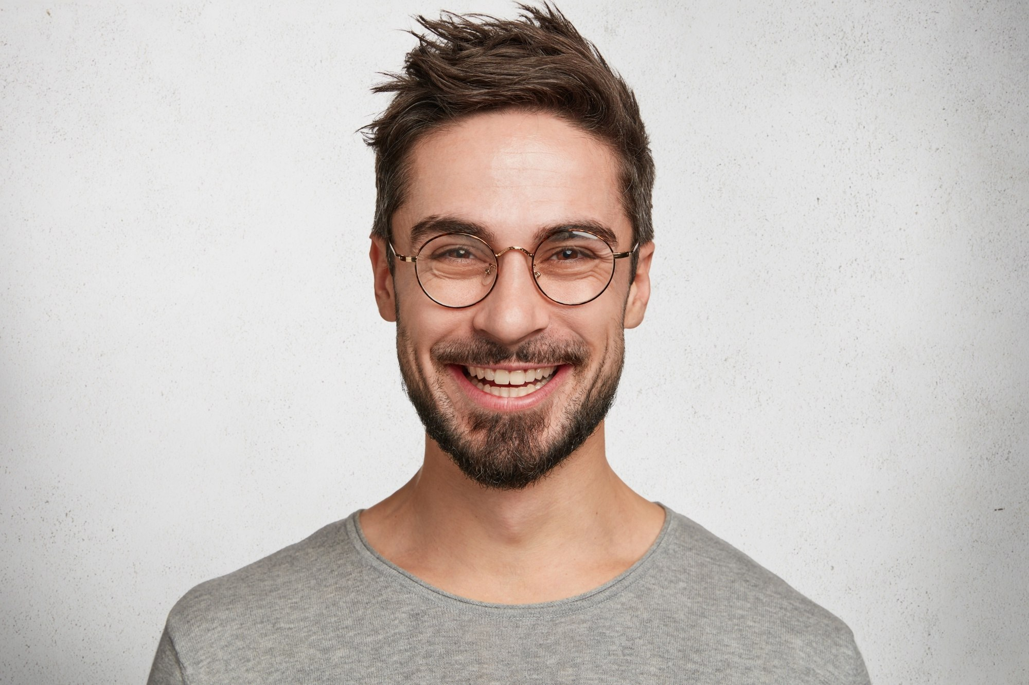 Messy hairstyles men: Closeup shot of a man with short brown messy hair and mustache wearing eyeglasses