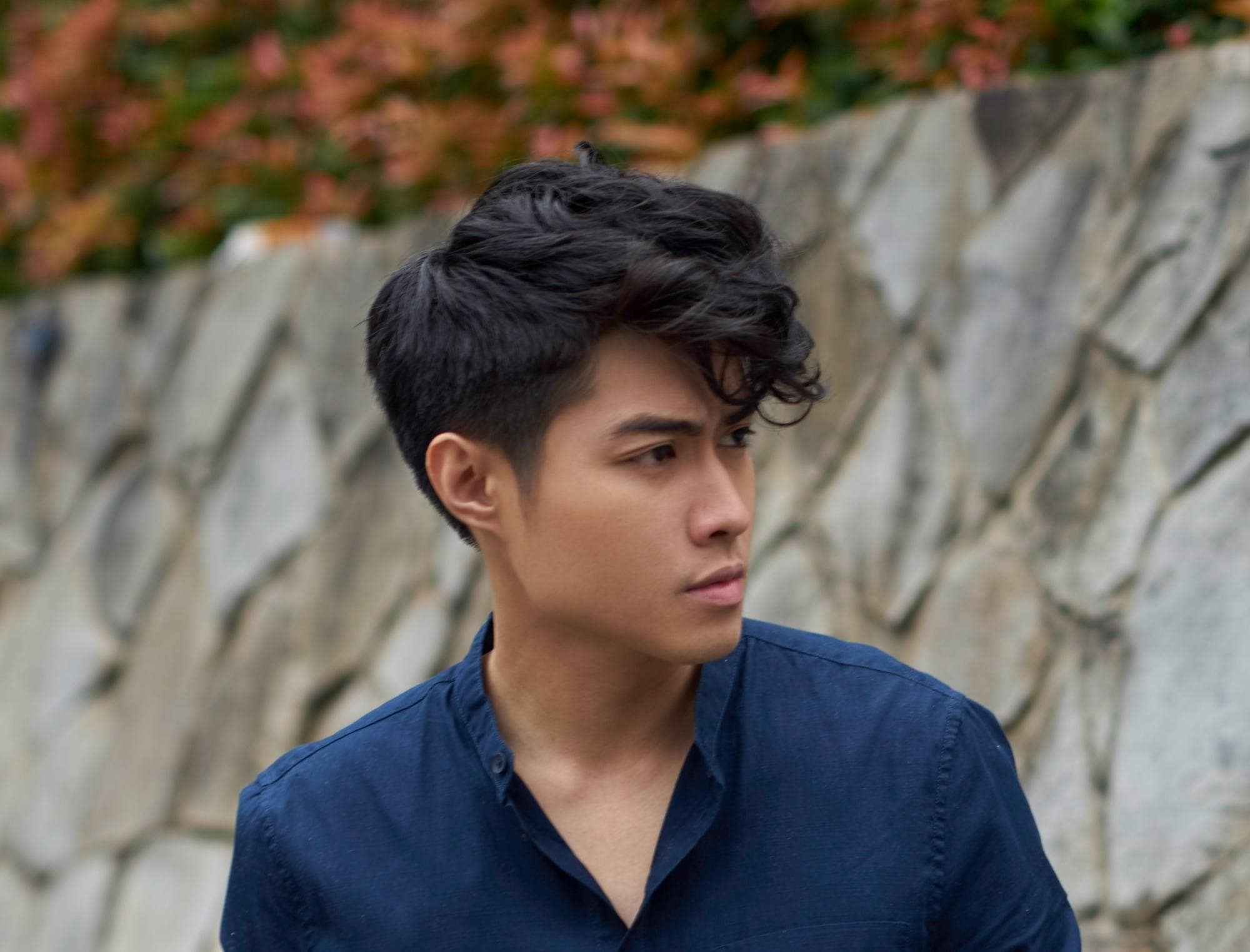 Messy hairstyles for men: Closeup shot of an Asian man with black textured wavy hair wearing a blue polo outdoors