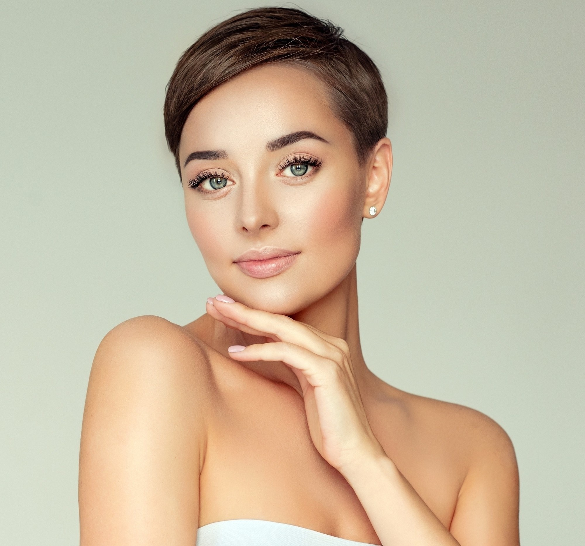 Short hairstyles for long faces: Closeup shot of a woman with short dark hair wearing a white tube top