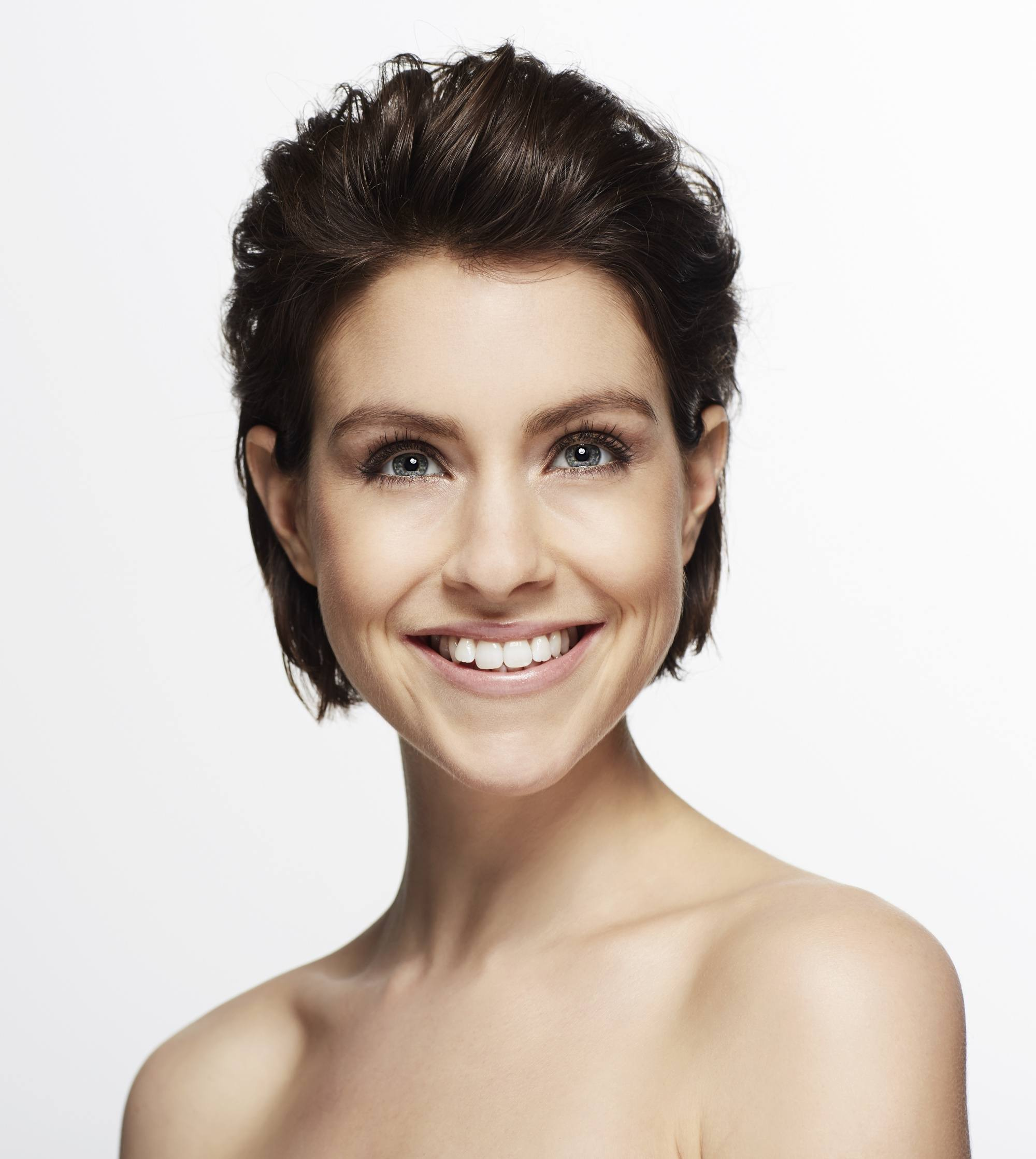 Short hairstyle for long faces: Closeup shot of a woman with short dark slicked back hair