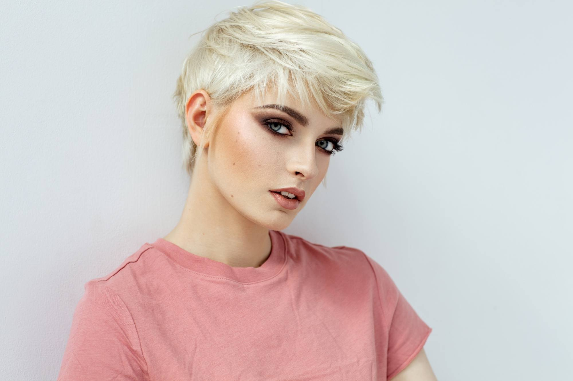 Short hairstyles for long faces: Closeup shot of a woman with short blonde hair wearing a pink shirt