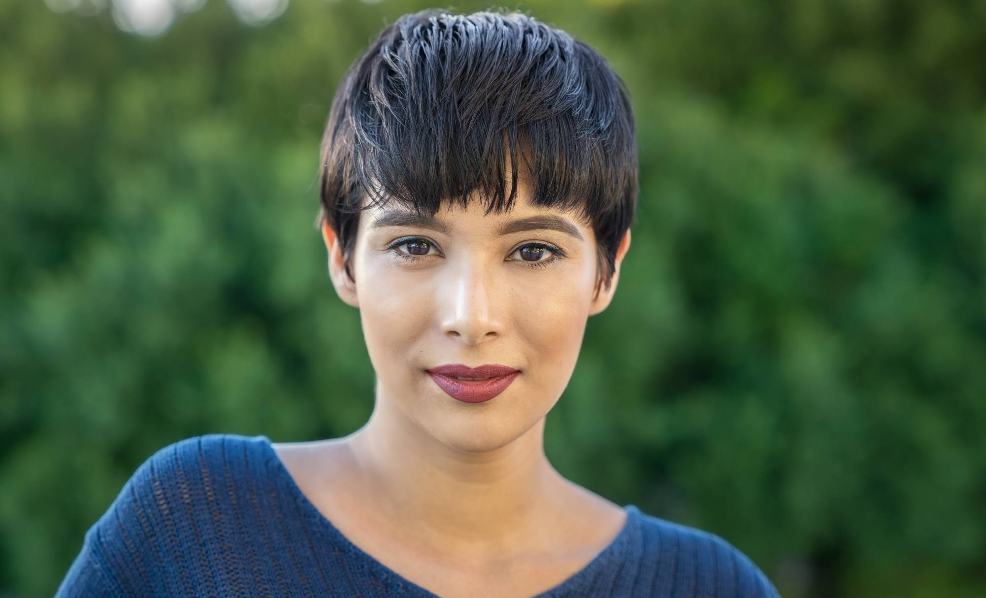Short hairstyles for long faces: Closeup shot of a woman with short black pixie cut wearing a blue top outdoors