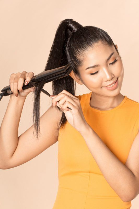 Sleek and fierce ponytail: Closeup shot of an Asian woman with long black hair in high ponytail ironing her hair