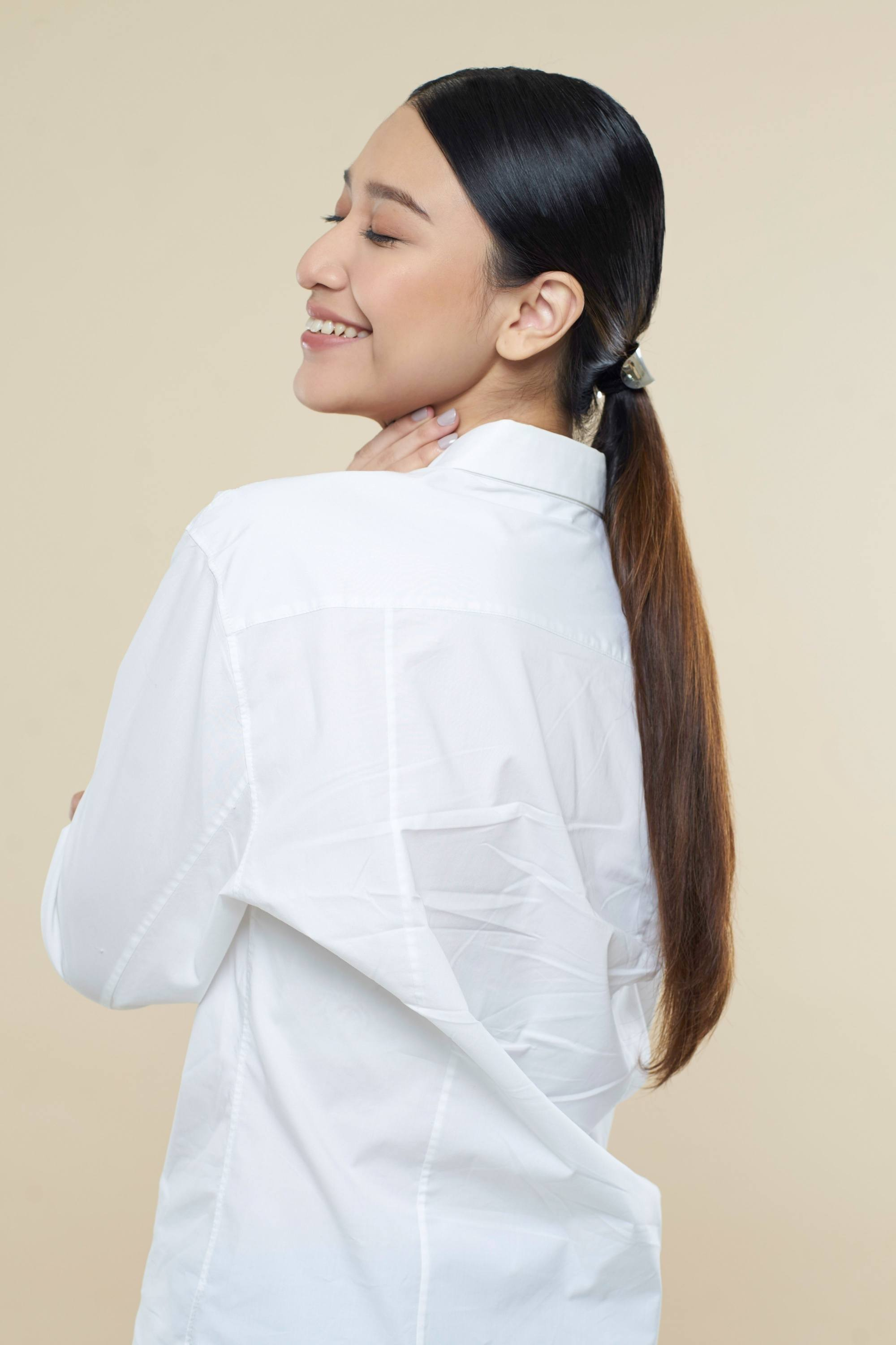 Sleek tied hair: Side view of an Asian woman with long dark hair in low ponytail wearing a white blouse