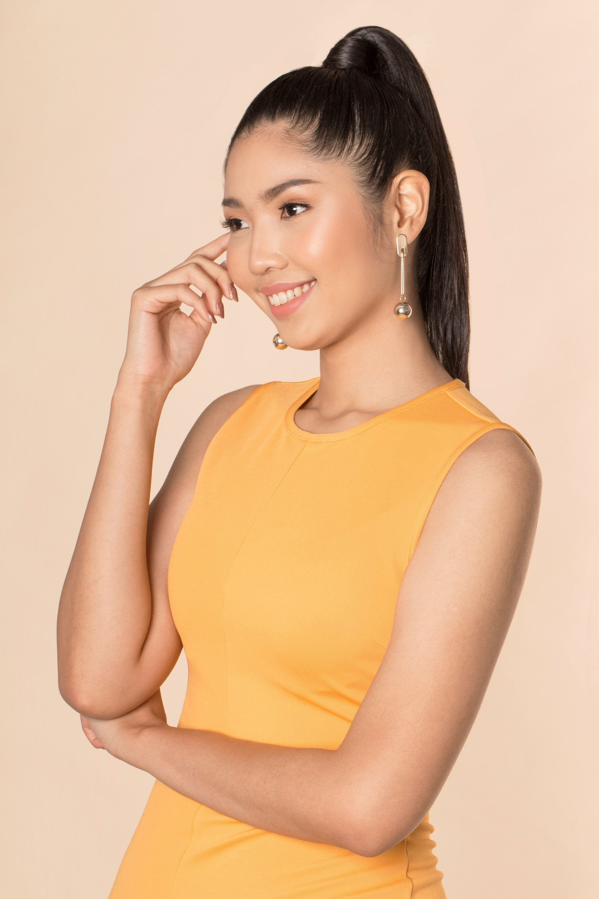 Sleek tied hair: Asian woman with long black hair in high ponytail wearing a mustard-colored sleeveless dress