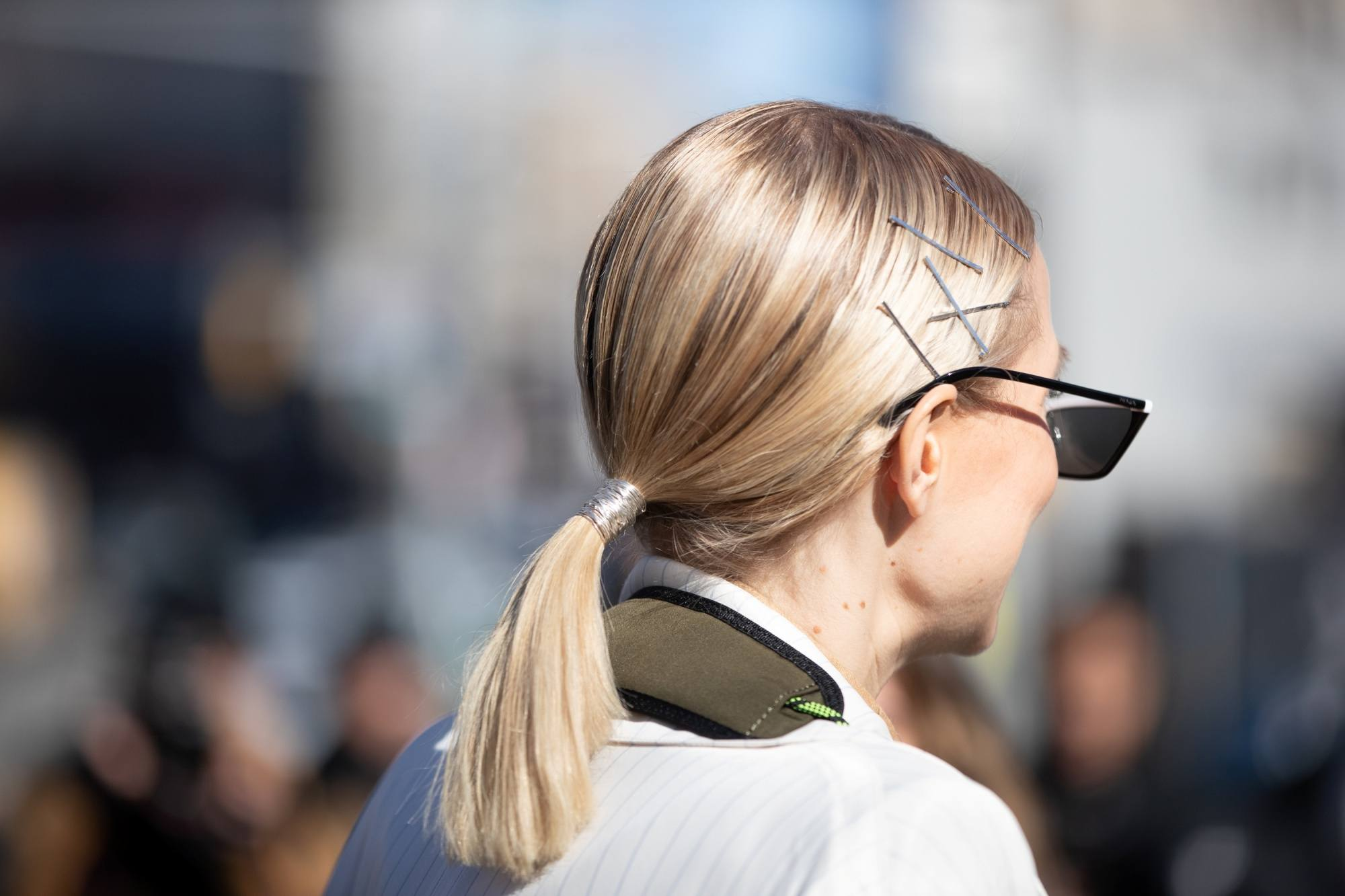 Sleek tied hair: Back side shot of a blonde woman with shoulder-length hair in low ponytail with bobby pins