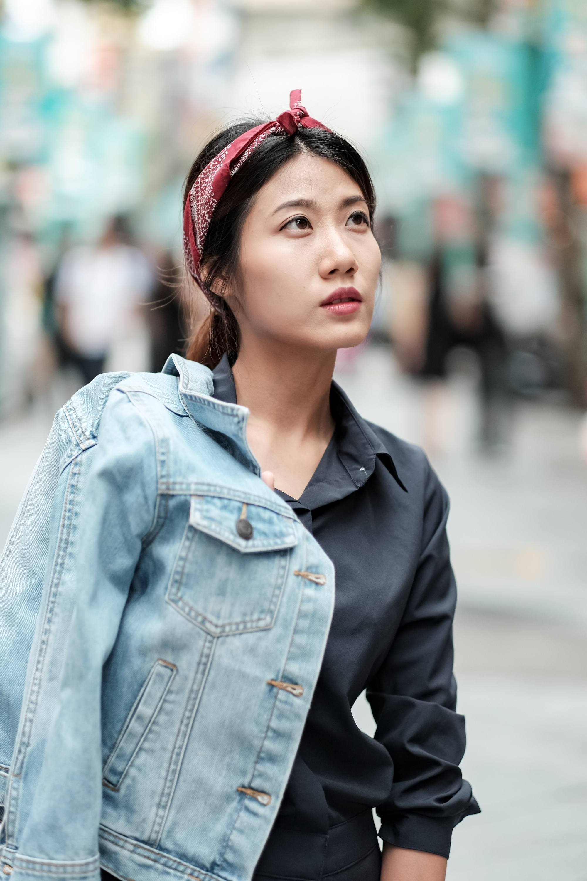 Sleek tied hair: Asian woman with long black hair in a ponytail with red headband wearing denim jacket outdoors