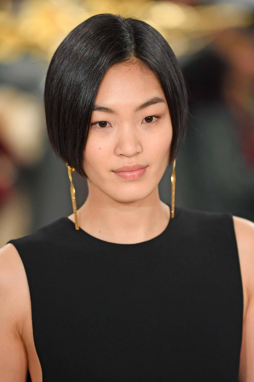 Straight bob: Closeup shot of an Asian woman with short black hair wearing a black dress