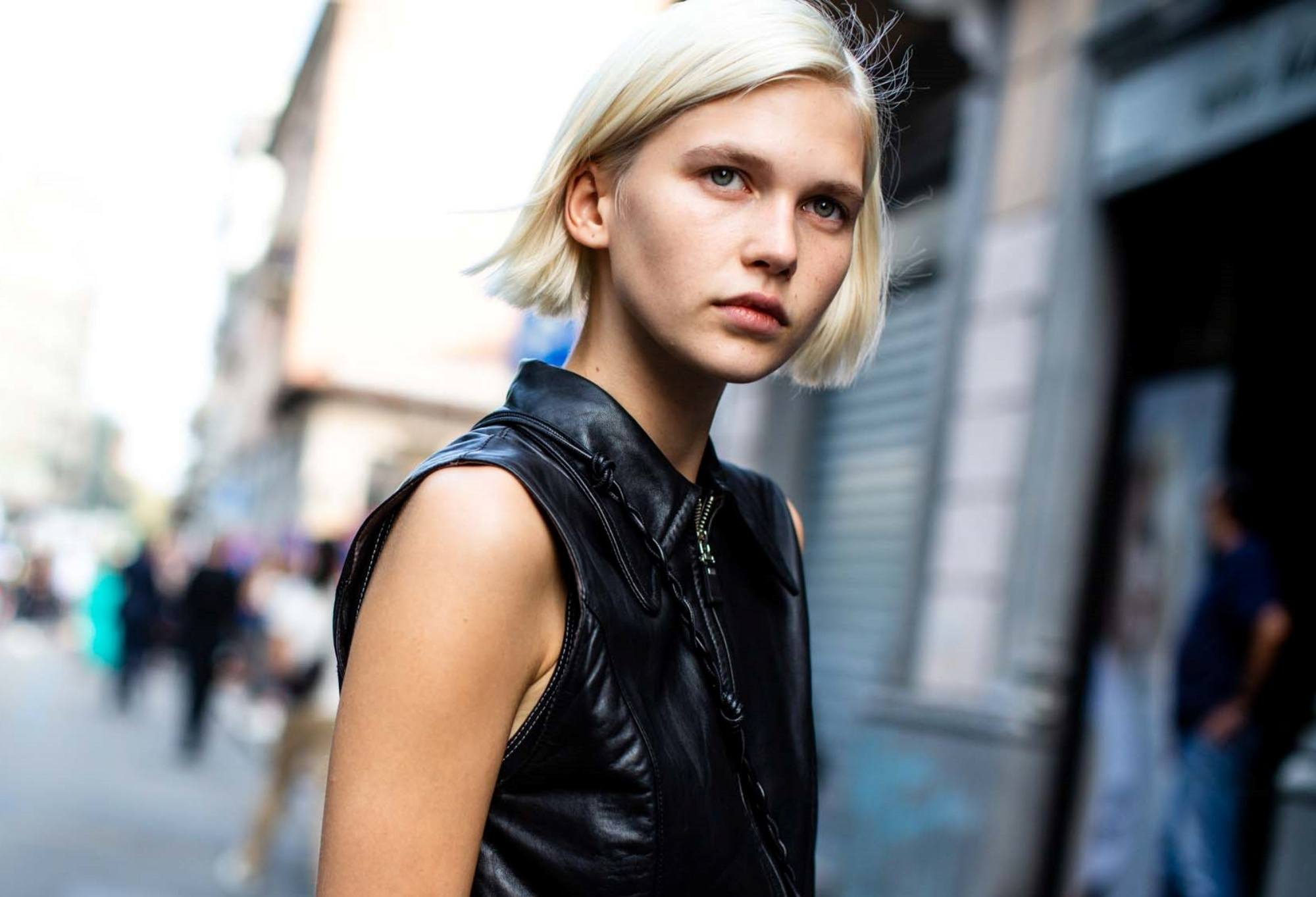 Straight bob: Closeup shot of a woman with short blonde hair wearing a sleeveless black top outdoors