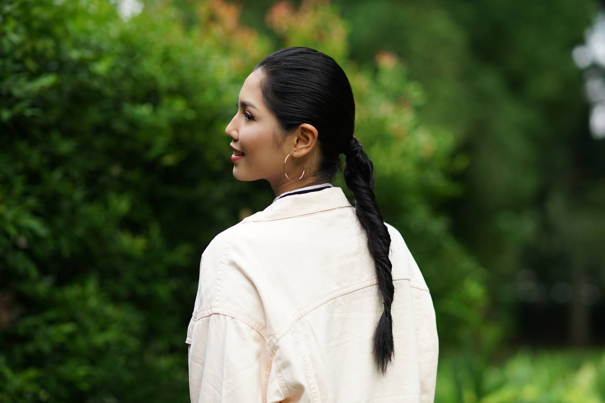 Summer-ready hair: Back shot of an Asian woman with long black hair in a double rope braid ponytail wearing a white jacket outdoors