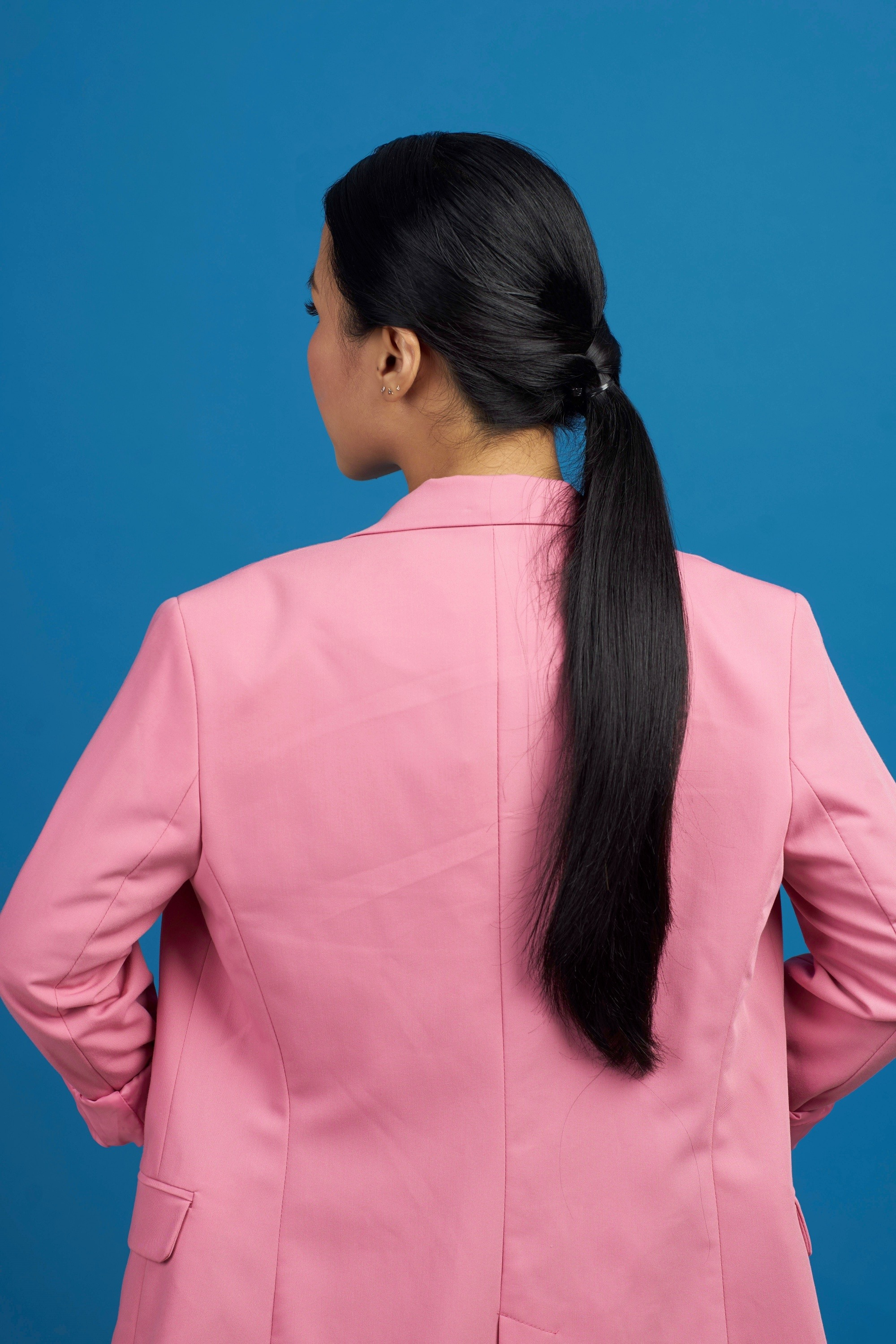 Vintage ponytail: Back shot of an Asian woman with long black hair in tucked in ponytail wearing a pink suit