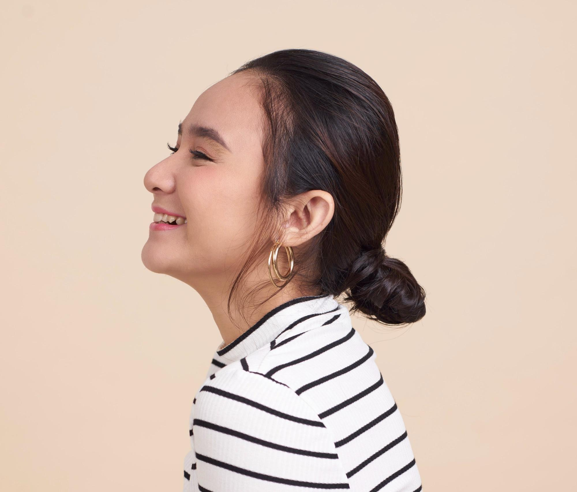 Closeup shot of an Asian woman with black hair in a low bun wearing a striped shirt