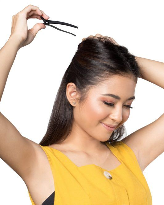 Bobby pin hair crown: Asian woman clipping the top section of her dark shoulder-length hair and smiling