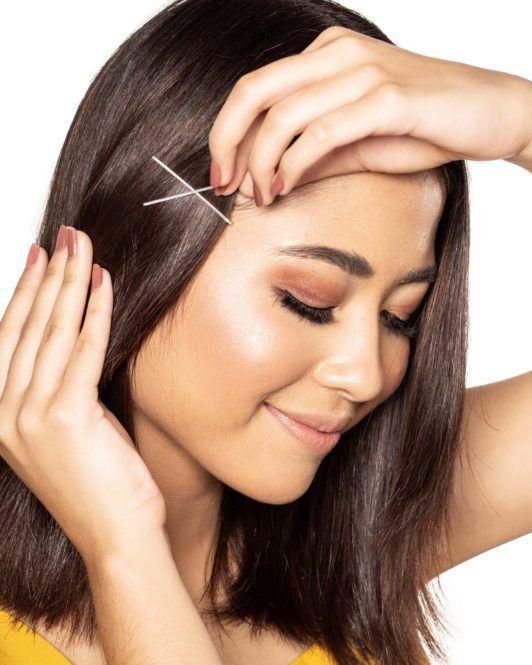 Bobby pin hair crown: Closeup shot of an Asian woman putting bobby pins on her dark hair