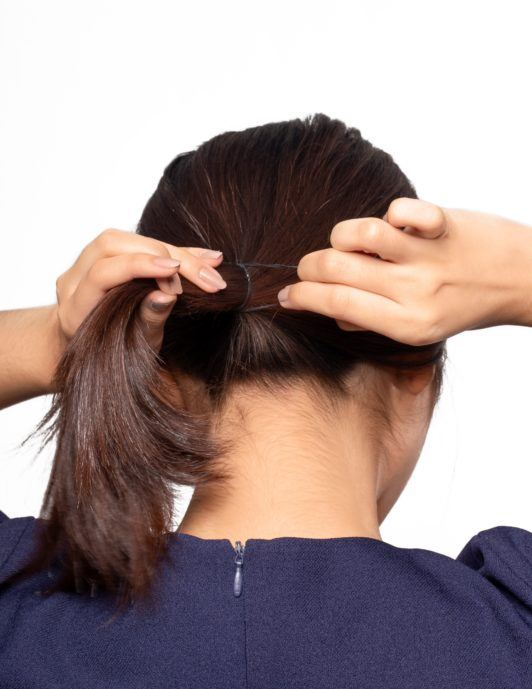 Chignon for short hair: Back shot of an Asian woman tying her dark hair into a low ponytail