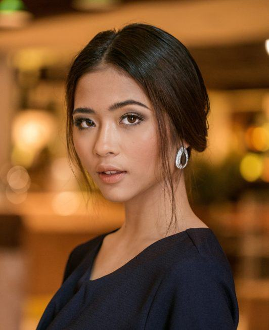 Chignon for short hair: Asian woman with dark hair in chignon standing in a luxurious lobby