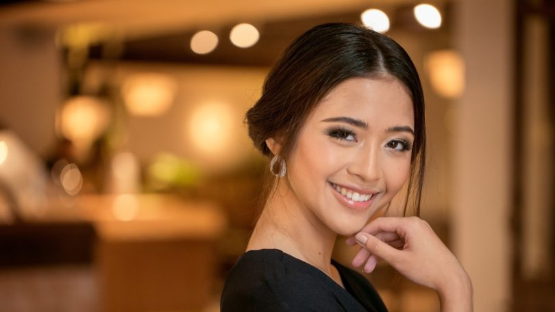 Chignon for short hair: Asian woman with dark hair in a chignon smiling in a hotel lobby