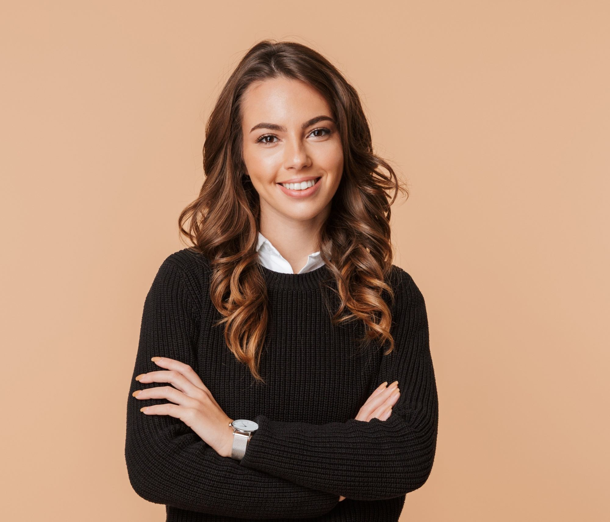 Golden brown hair color: Woman with long wavy brown hair wearing a black shirt against a peach backdrop