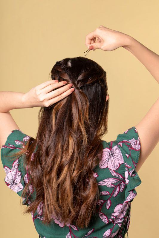 Half up boho braid: Back shot of an Asian woman with long dark brown hair pinning boho braids