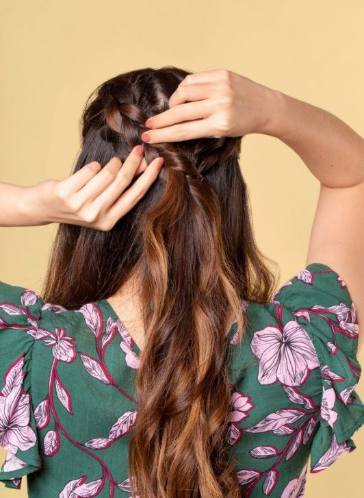 Half up boho braid: Back shot of an Asian woman with long dark brown hair pulling the sides of her braid