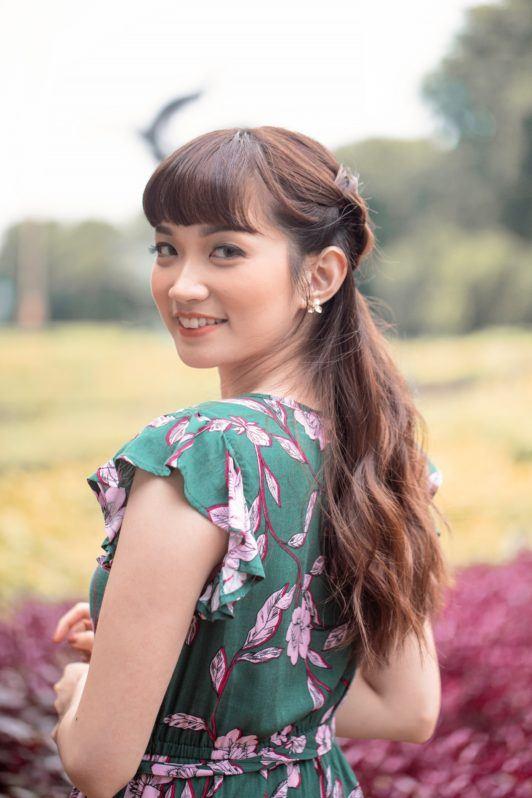 Half up boho braid: Closeup shot of an Asian woman with long dark brown hair in half up boho braid smiling outdoors