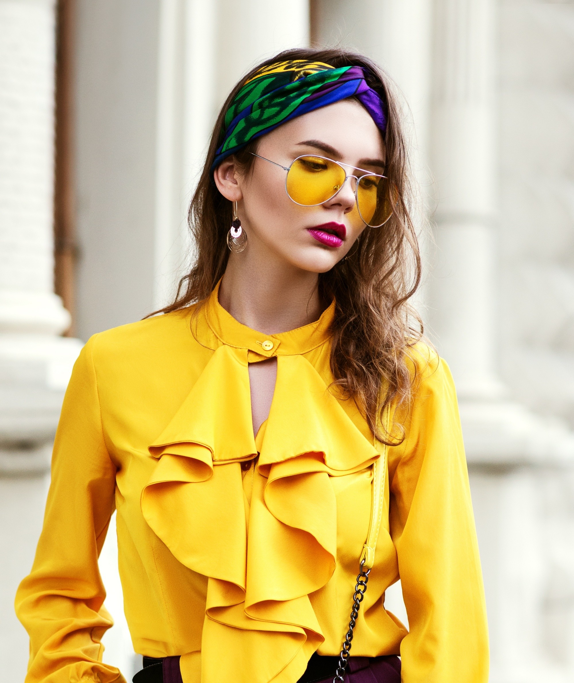 Headband hairstyles: Woman with long brown wavy hair wearing a headband and yellow blouse outdoors