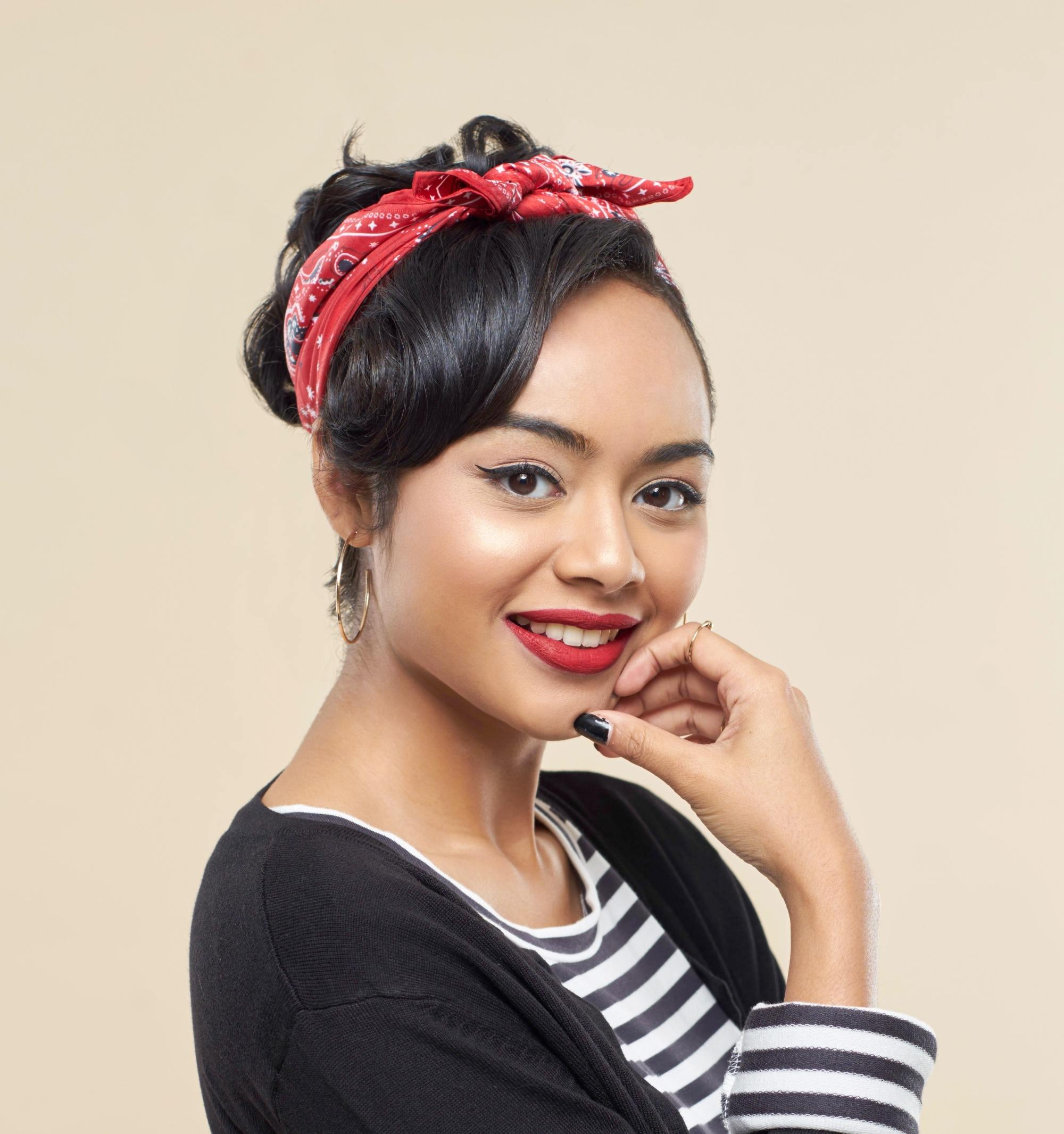 Headband hairstyles: Closeup shot of an Asian woman with black hair in an updo wearing a red headband