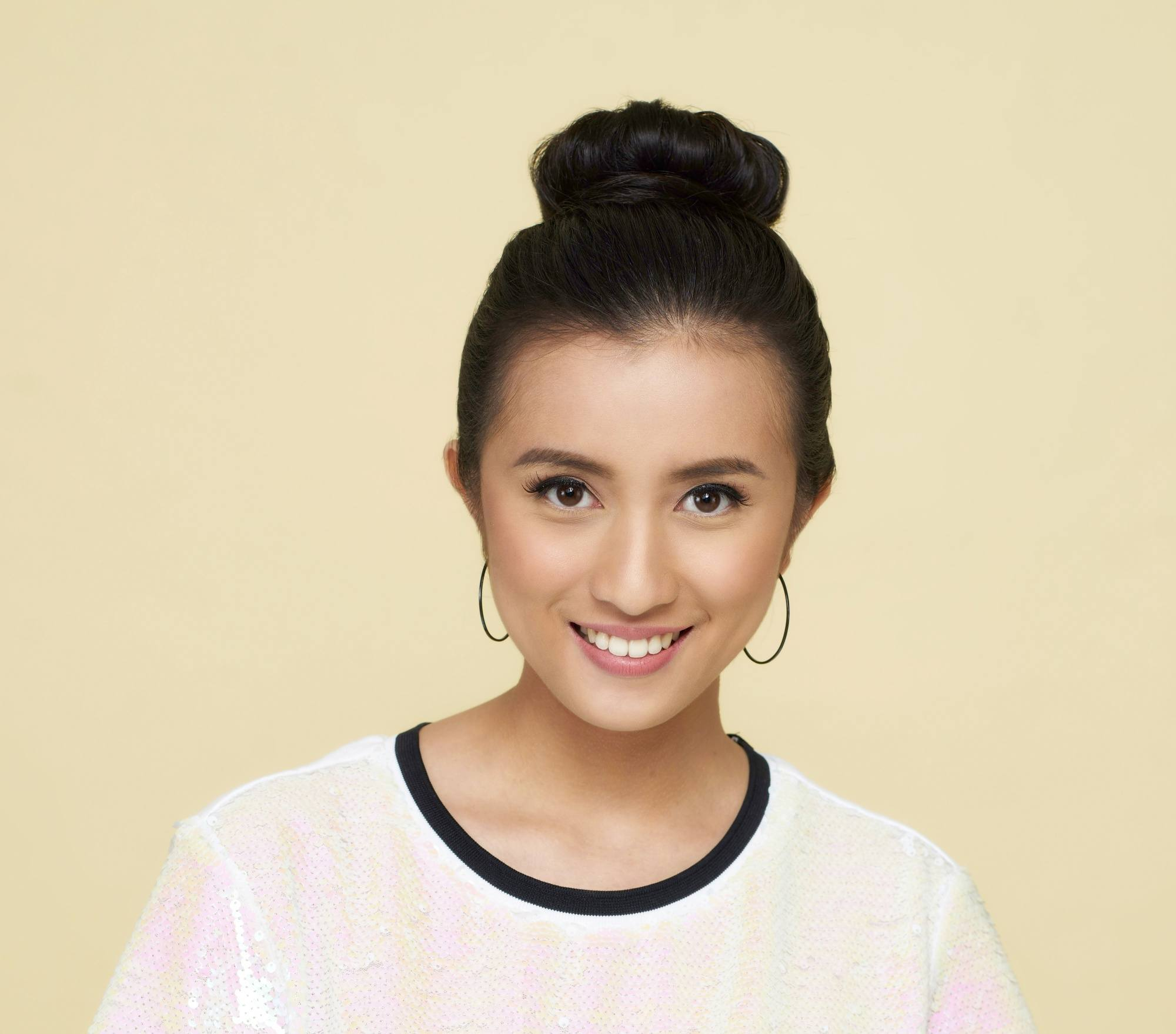 Asian woman with black hair in a hair donut bun wearing a white shirt and hoop earrings